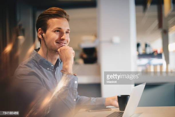 Thoughtful businessman sitting with hand on chin at desk in office
