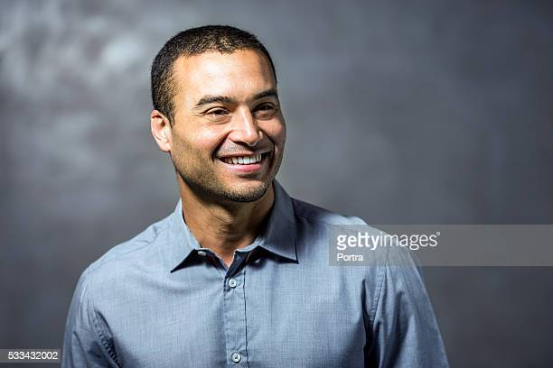 Thoughtful businessman smiling against wall