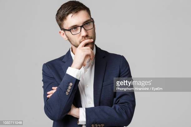 thoughtful businessman standing against gray background - mano en la barbilla fotografías e imágenes de stock