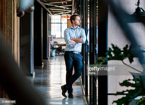 Durchdachte Geschäftsmann stehend Arme verschränkt im Büro