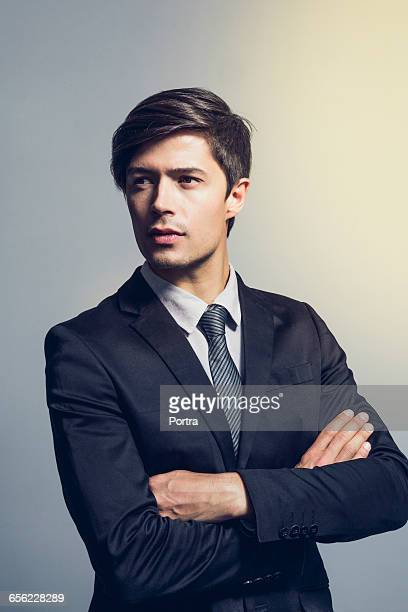 thoughtful businessman standing arms crossed - bem vestido - fotografias e filmes do acervo