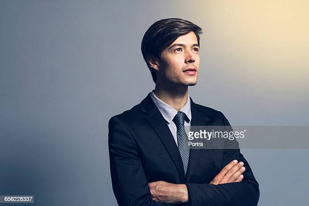 Thoughtful businessman standing arms crossed