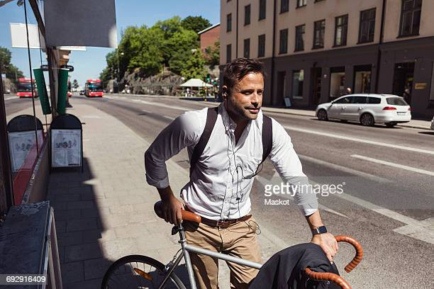 Thoughtful businessman standing with bicycle on sidewalk in city