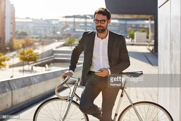 thoughtful businessman standing with bicycle - uomini di età media foto e immagini stock