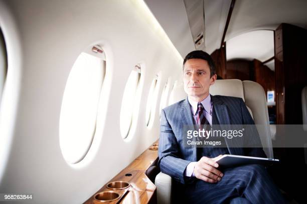 thoughtful businessman traveling in corporate jet - private aeroplane stock pictures, royalty-free photos & images