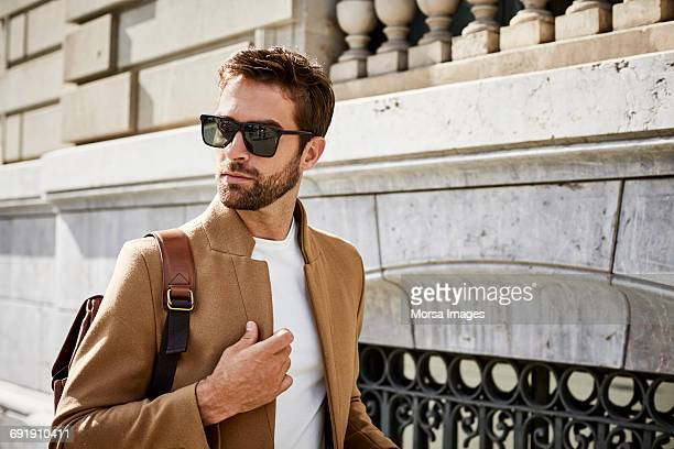 thoughtful businessman with bag looking away - shoulder bag stock pictures, royalty-free photos & images