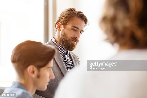 Thoughtful businessman with colleagues