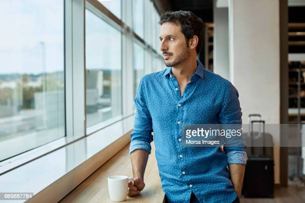 thoughtful businessman with cup at window sill - 35 39 years stock pictures, royalty-free photos & images