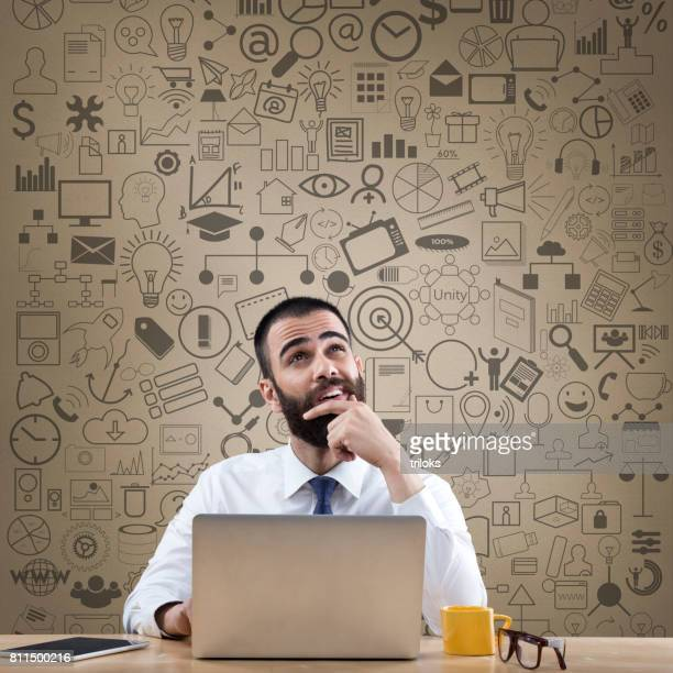 Thoughtful businessman with laptop at office desk