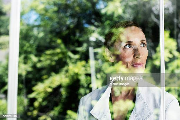 thoughtful businesswoman by glass window - tranquility stock pictures, royalty-free photos & images