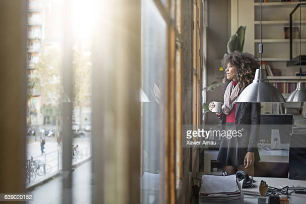 Thoughtful businesswoman holding coffee cup