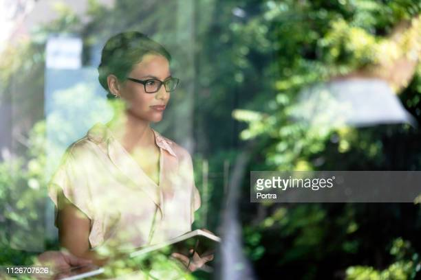 thoughtful businesswoman holding diary in office - photographed through window stock pictures, royalty-free photos & images