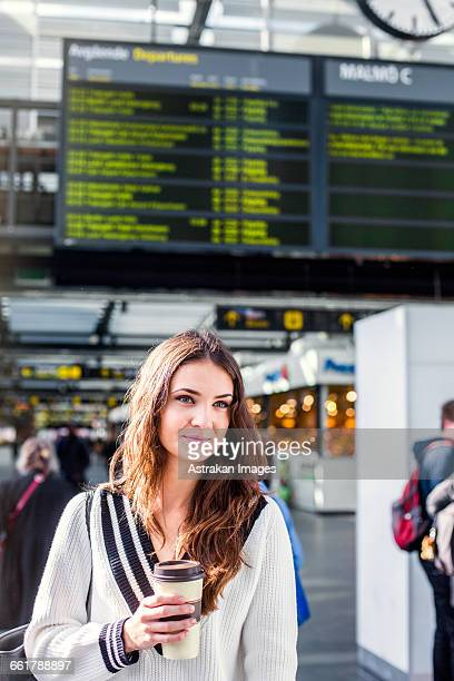 Thoughtful businesswoman holding disposable cup at railroad station