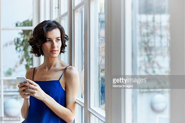 Thoughtful businesswoman holding mobile phone
