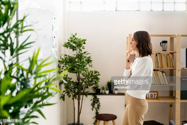 thoughtful businesswoman looking at whiteboard while standing at office - business plan stock pictures, royalty-free photos & images
