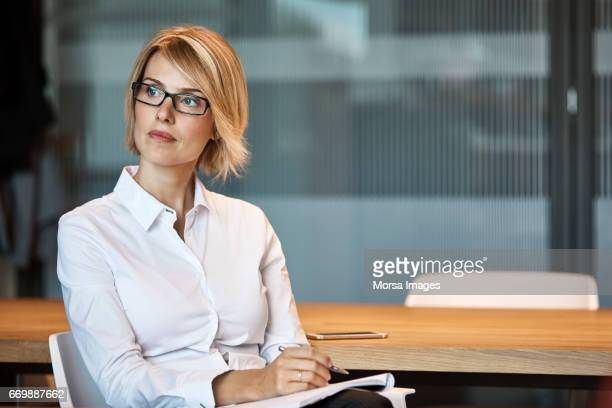 thoughtful businesswoman looking away at desk - part of a series stock pictures, royalty-free photos & images
