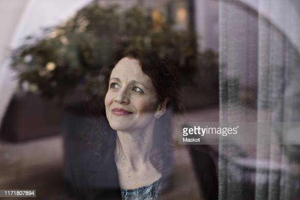 thoughtful businesswoman looking away seen through glass window - photographed through window stock pictures, royalty-free photos & images