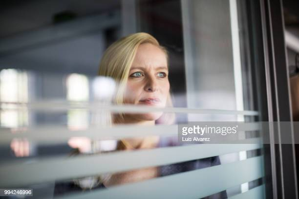 Thoughtful businesswoman looking through glass