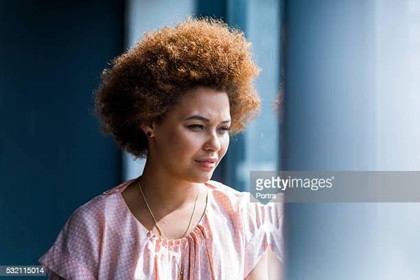 Durchdachte Geschäftsfrau Blick durchs Fenster