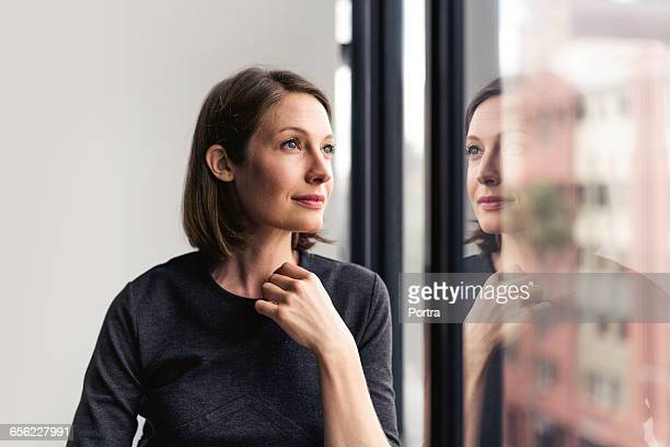thoughtful businesswoman looking through window - spiegelung stock-fotos und bilder