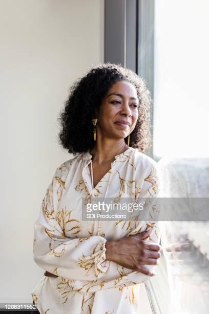 mujer de negocios pensada mira por la ventana de la oficina - blouse fotografías e imágenes de stock