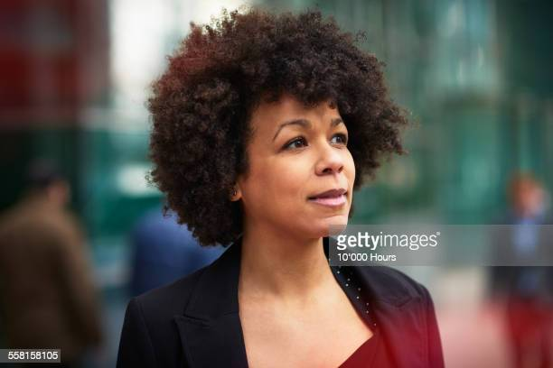 thoughtful businesswoman on busy street - mature women stock pictures, royalty-free photos & images