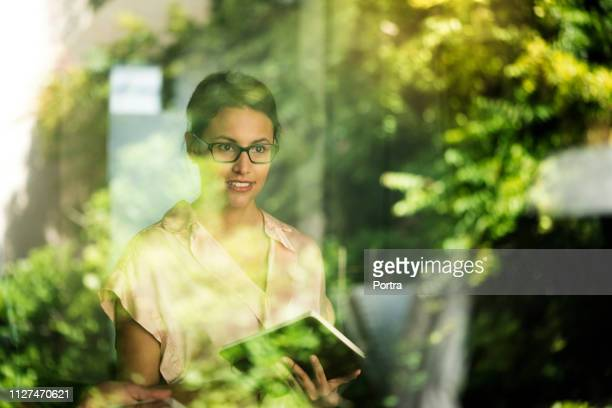 thoughtful businesswoman seen through window - environment stock pictures, royalty-free photos & images