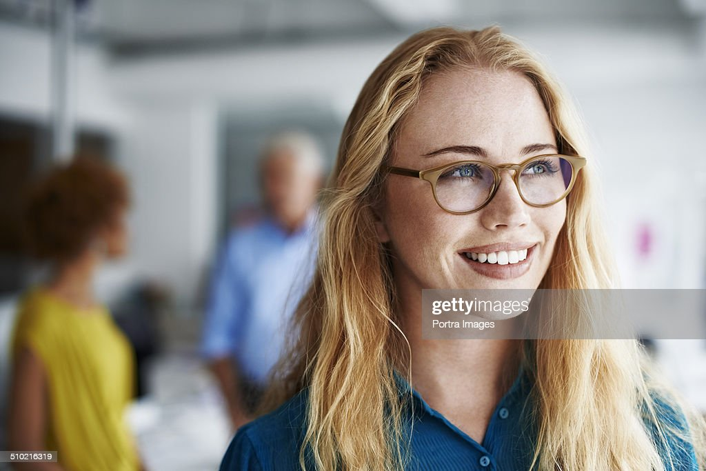 Thoughtful businesswoman smiling in office : Stockfoto