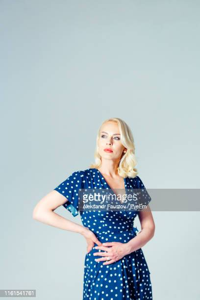 thoughtful businesswoman standing against white background - polka dot stock pictures, royalty-free photos & images