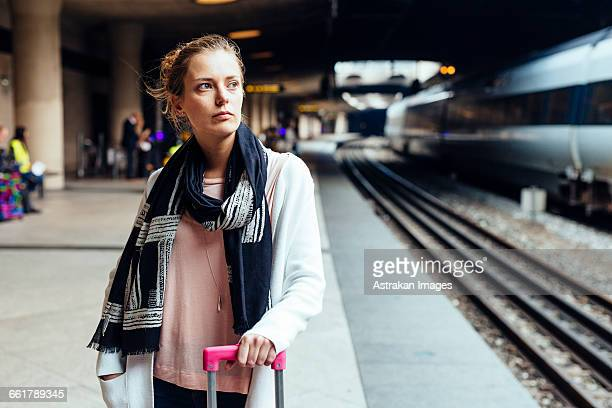 Thoughtful businesswoman standing at railway station