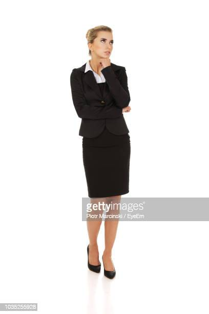 thoughtful businesswoman standing over white background - 若い女性だけ ストックフォトと画像