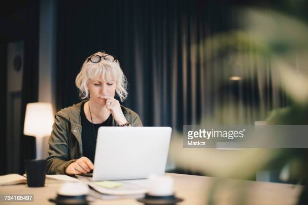 Thoughtful businesswoman using laptop at desk in office