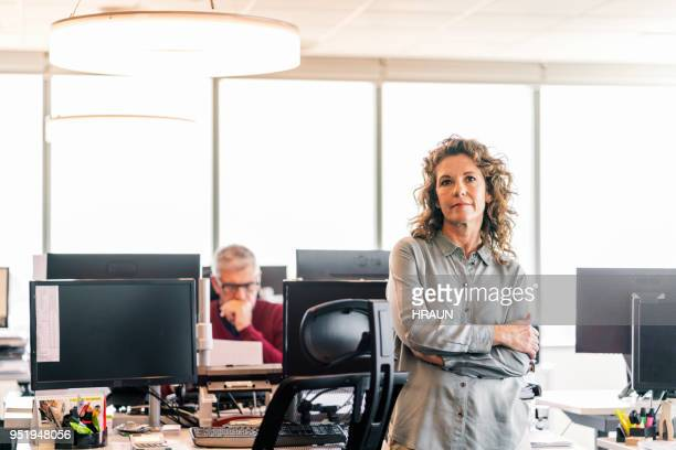 Thoughtful businesswoman with arms crossed at desk