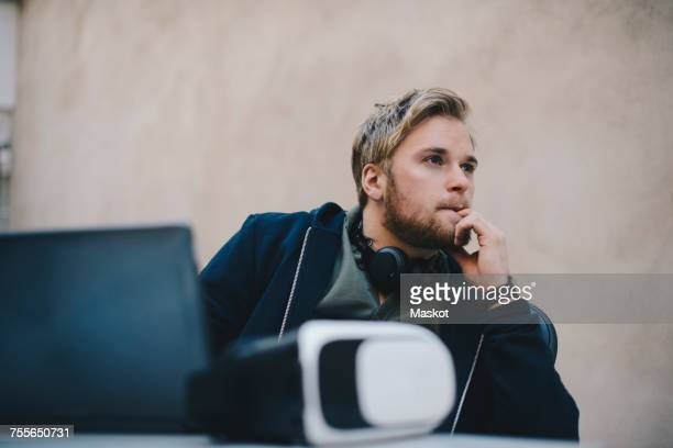 Thoughtful computer programmer looking away while sitting at desk in office