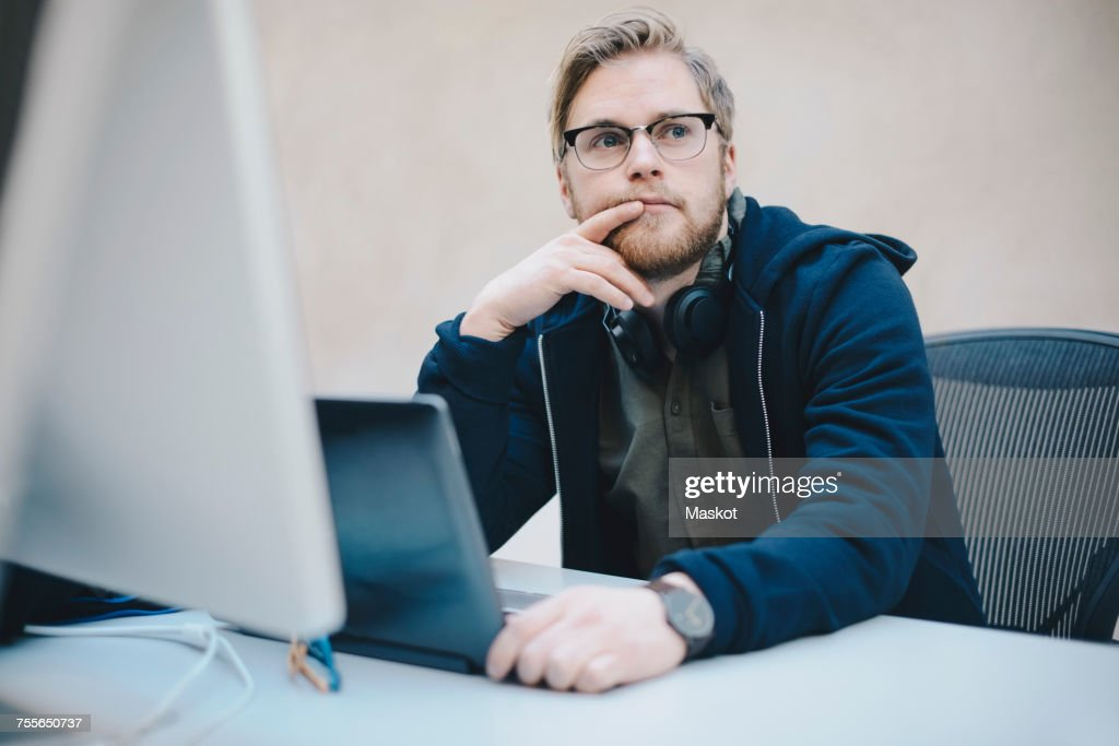 Thoughtful computer programmer sitting at desk in office : Stock Photo