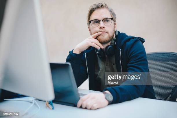 Thoughtful computer programmer sitting at desk in office