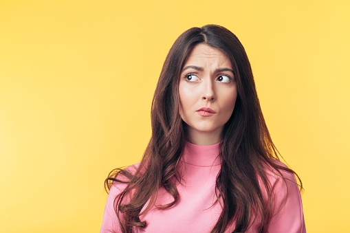 Thoughtful confused woman looking away isolated over yellow background 1138637857