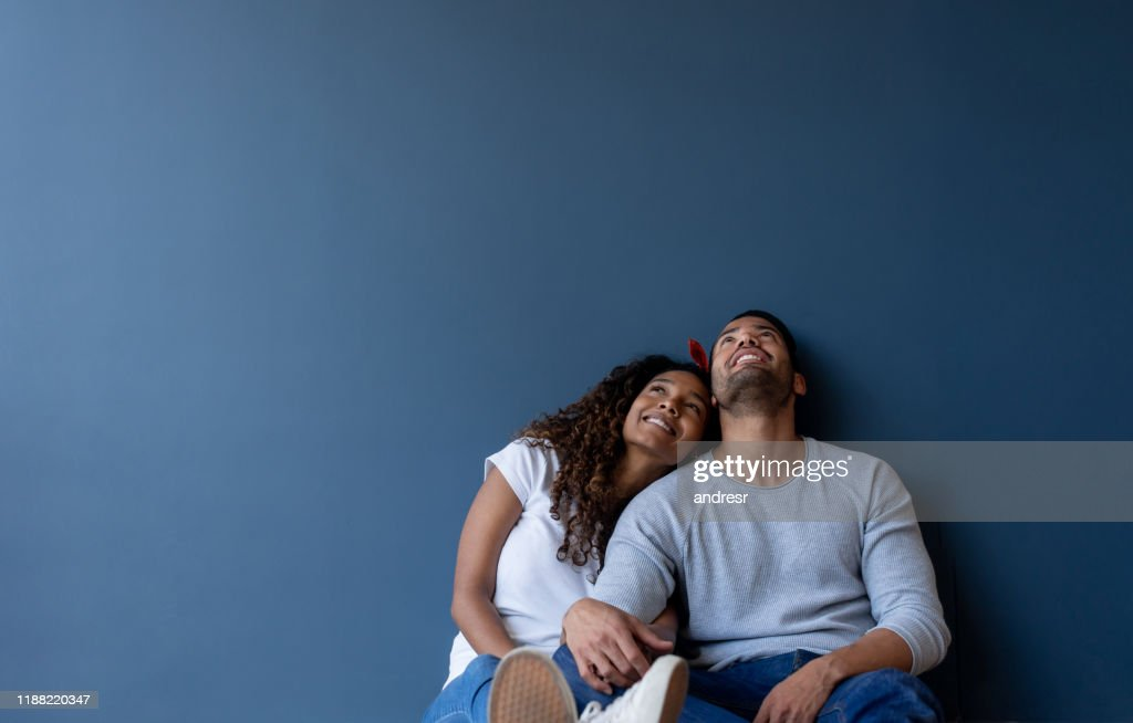 Thoughtful couple at home leaning against a wall and smiling : Stock Photo