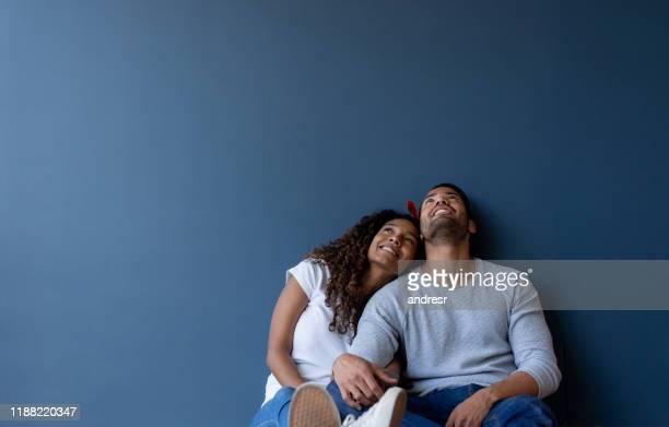 couples pensifs à la maison se penchant contre un mur et souriant - rêvasser photos et images de collection