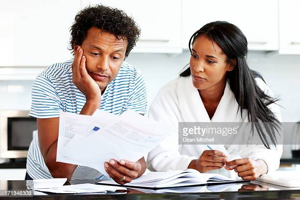 Thoughtful couple calculating their monthly expenses