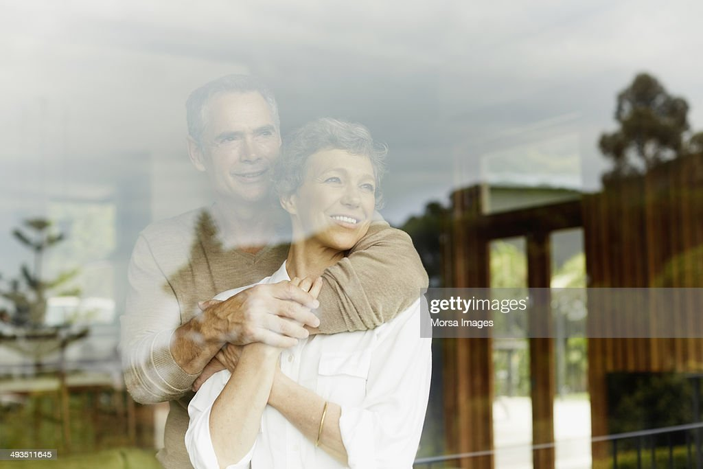 Thoughtful couple looking through window : ストックフォト