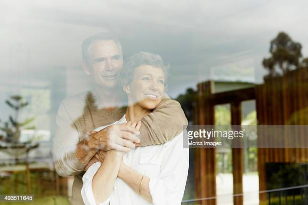 thoughtful couple looking through window - outdoors stock-fotos und bilder