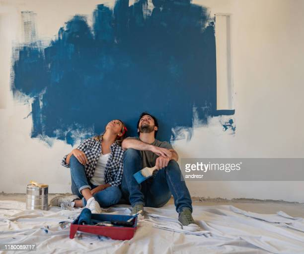 thoughtful couple painting their house - young couple stock pictures, royalty-free photos & images