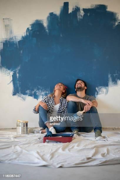 nachdenkliches paar, das eine pause vom malen ihres hauses - dekorieren stock-fotos und bilder
