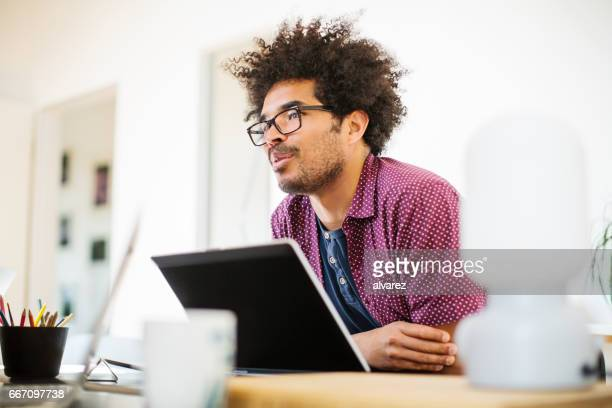 Thoughtful creative businessman at desk in office