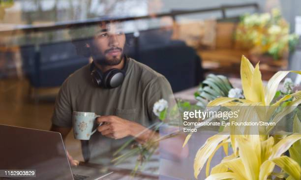 thoughtful creative businessman using laptop in open plan office - convenience stock pictures, royalty-free photos & images