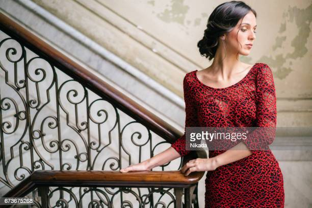 Thoughtful cuban woman standing on steps against wall