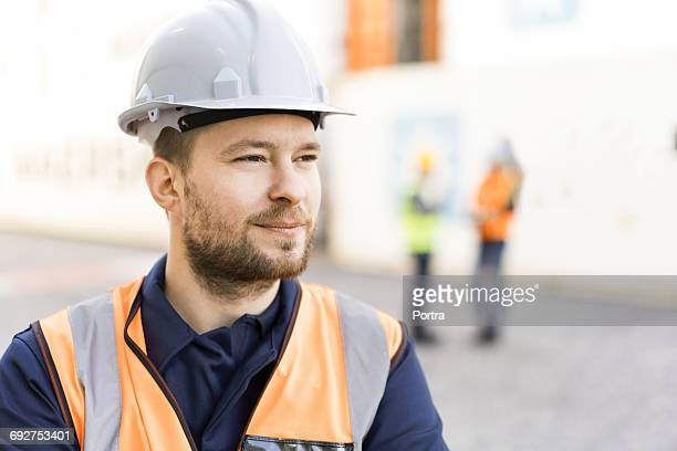 thoughtful dock worker wearing hardhat in shipyard - schutzhelm stock-fotos und bilder