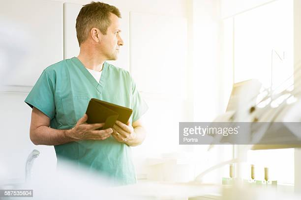 Thoughtful doctor holding digital tablet in clinic