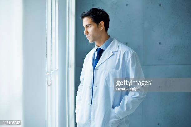 Thoughtful doctor looking through a window